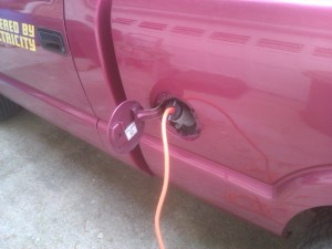A 240 volt cable plugged into a truck's gas cap area.