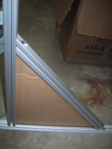 A right triangle of cardboard contained within the T-Slots of the 80/20 frame.