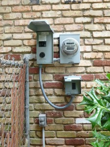 electrical boxes and meter mounted on a brick wall