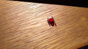 Small red LED with legs bent back around towards the front